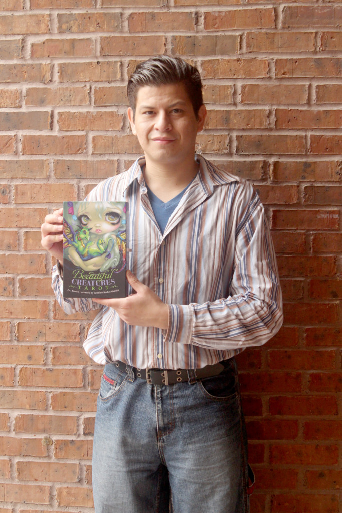 """Jose Rolando Rivera holds the book """"Beautiful Creatures Tarot."""" Rivera contributed ideas to his publisher to produce the cover."""