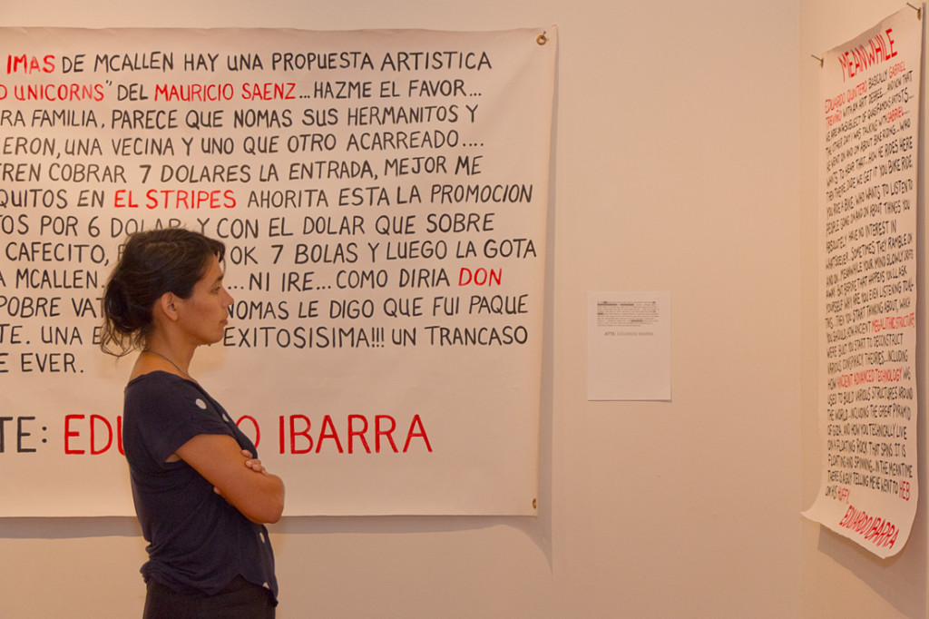 """Visitor Cristina Houle reads """"MEANWHILE,"""" one of the """"narcomantas"""" featured in the exhibition./Mario Gonzalez/The Rider Photos"""