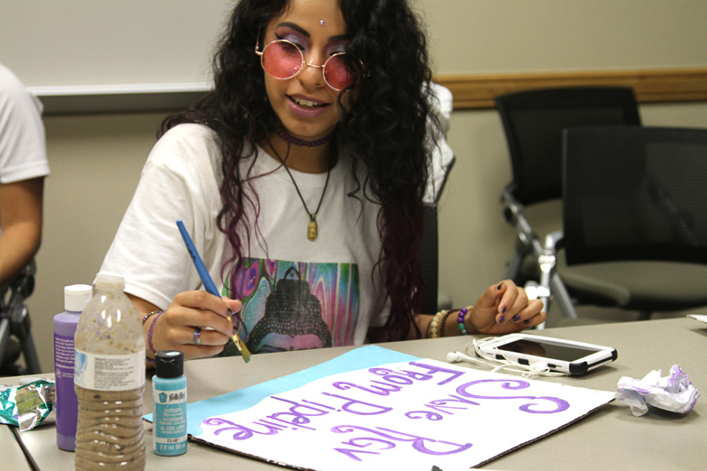 Film major Romany Manriquez works on an anti-LNG poster during the Environmental Awareness Club meeting last Thursday in Edinburg./Sarah Carvajal/The Rider