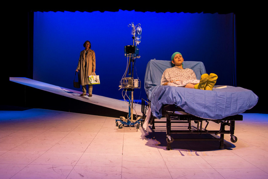 "Vivian Bearing (portrayed by Ana Laura Chavez) lays unconscious in a hospital bed while her literature mentor, E.M. Ashford (portrayed by Kathy Raines) enters the scene. The production of ""Wit"" opened the 53rd season of the Camille Playhouse in Brownsville./P hoto Courtrtesy Camille Playhouse"