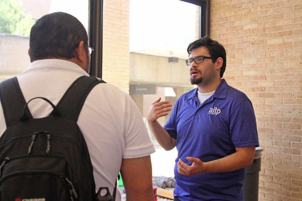 Psychology senior Alvaro Hernandez learns about cyber security from Alexander Valdez, director of community outreach for the Association of Information and Technology Preparation, last Tuesday at the University Ballroom on the Edinburg campus. /Lesley Robles/ The Rider