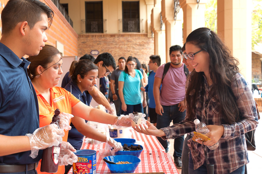 Biomedical sciences freshman Isabel Morales gets an ice cream cup Sept. 26 at the Student Union veranda on the Brownsville campus. The Vaquero Ice Cream Bar, hosted by the Student Union, featured different ice cream flavors and toppings./Mario Gonzalez/The Rider