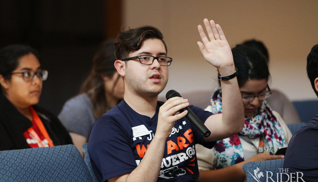 A picture of a young man raising his hand during a forum