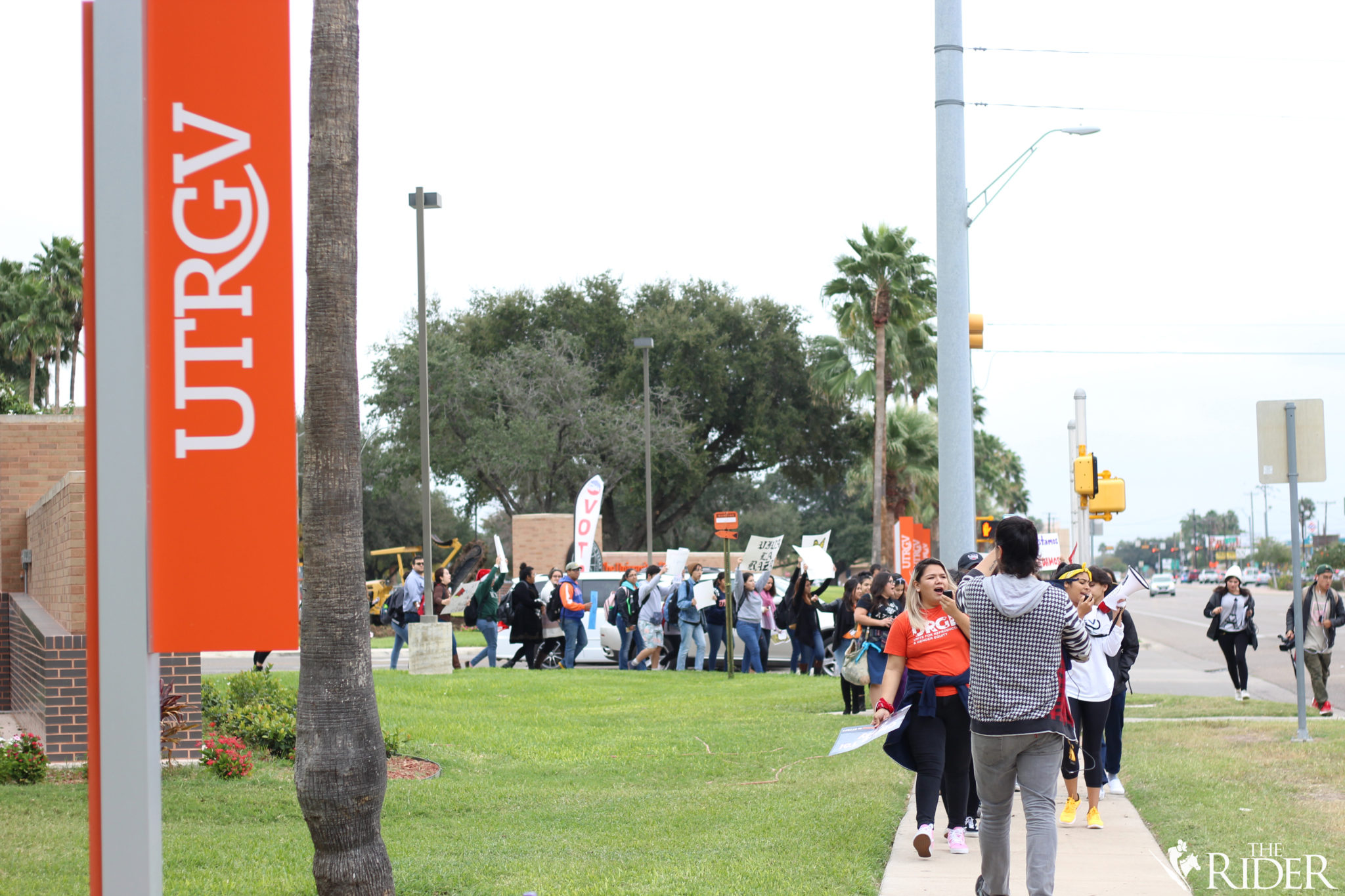 """Protesters march to the corner of Sugar Road and University Boulevard during the """"Solidarity Walkout"""" earlier today."""