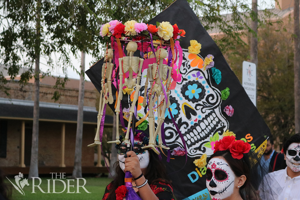 A colorful Día de los Muertos poster and plastic skeletons were among the items carried in the parade.