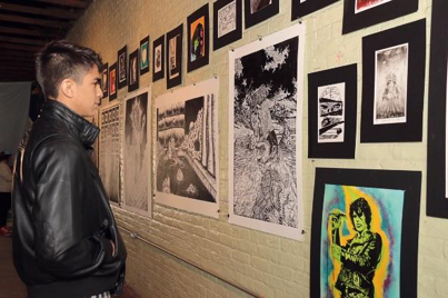 Rolando Torres views a print during last year's #Subculture: Urban Art Experience. The exhibit, held at the Brownsville Arts and Musicians building on East Adams Street, featured a silk screening and linoleum print workshop.